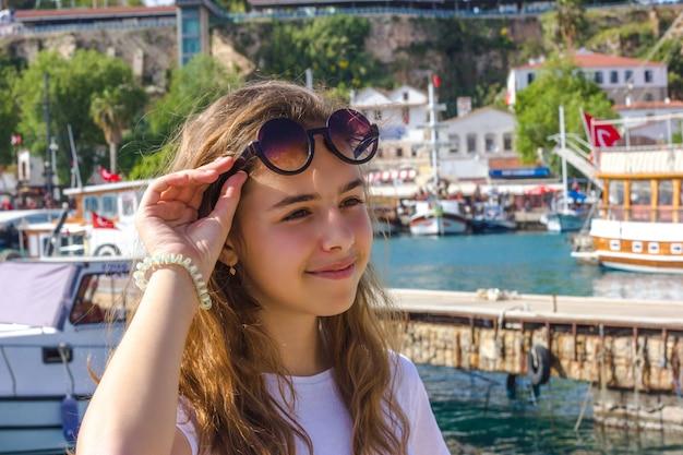 Junges mädchen mit dem langen haar auf dem pier im yachthafen