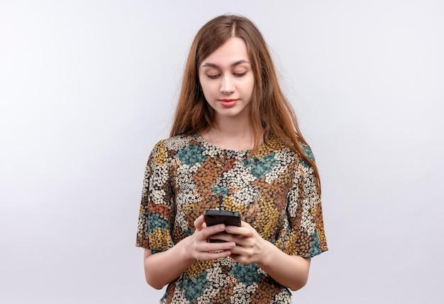 Junges mädchen mit dem langen haar, das buntes kleid hält, das smartphone hält, das mit jemandem mit ernstem selbstbewusstem ausdruck auf gesicht chattet
