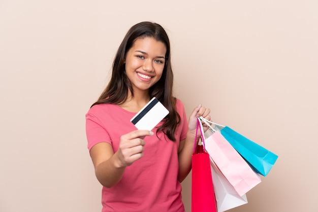Junges mädchen mit der einkaufstasche, die einkaufstaschen und eine kreditkarte hält