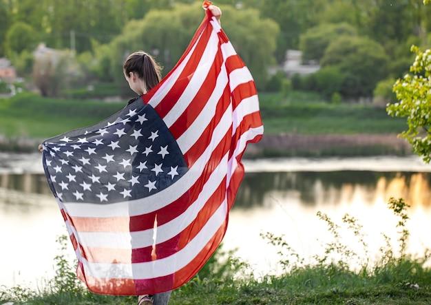 Junges mädchen mit der flagge von amerika auf natur von hinten.