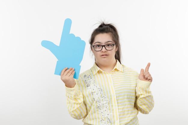 Junges mädchen mit einem down-syndrom, das handzeichen hält