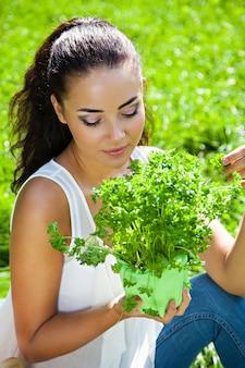 Junges mädchen mit einem korb von gemüse und früchten am picknick im freien, gesundes lebensmittelkonzept