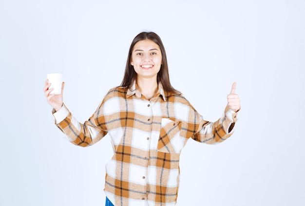 Junges mädchen mit einer tasse tee daumen aufgeben auf weiße wand.