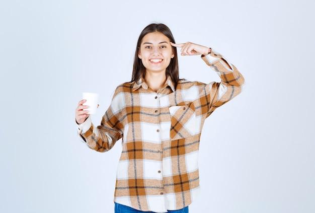 Junges mädchen mit einer tasse tee, die auf sich selbst auf weiße wand zeigt.