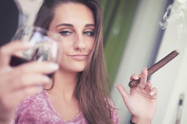 Junges mädchen mit einer zigarre und einem glas alkohol