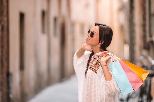 Junges mädchen mit einkaufstaschen auf schmaler straße in europa.