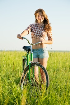Junges mädchen mit fahrrad im gras