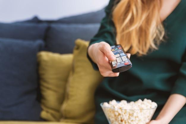 Junges mädchen mit fernsehdirektübertragung und einem popcorn zu hause