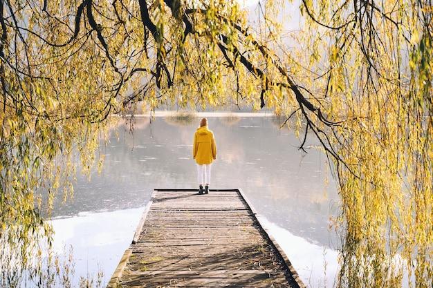 Junges mädchen mit gelbem regenmantel mit blick auf see oder teich in der natur