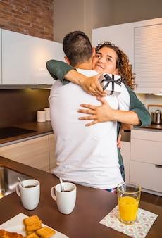 Junges mädchen mit geschenkbox in den händen umarmt ihren freund für eine schöne überraschung beim frühstück in der heimischen küche