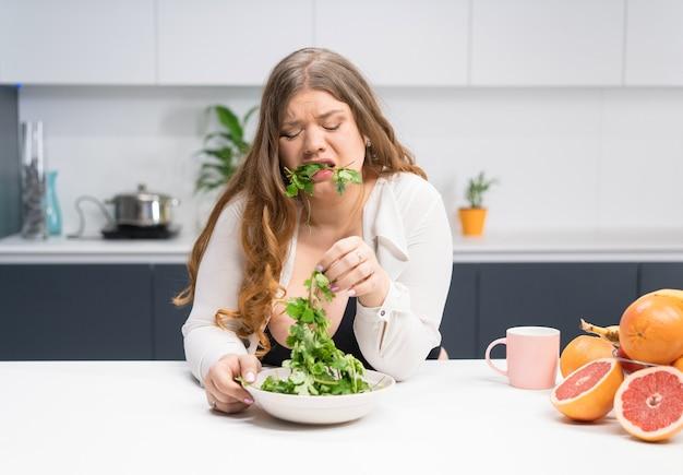 Junges mädchen mit gewichtsproblemen, die frischen salatguss halten, der versucht, ihn zu kauen