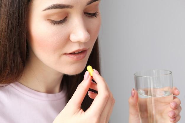 Junges mädchen mit guter laune nimmt tabletten zu hause ein