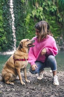 Junges mädchen mit ihrem hund, der in der natur geht