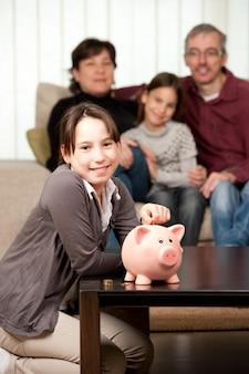 Junges mädchen mit ihren eltern und tochter, die geld auf einem sparschwein sparen