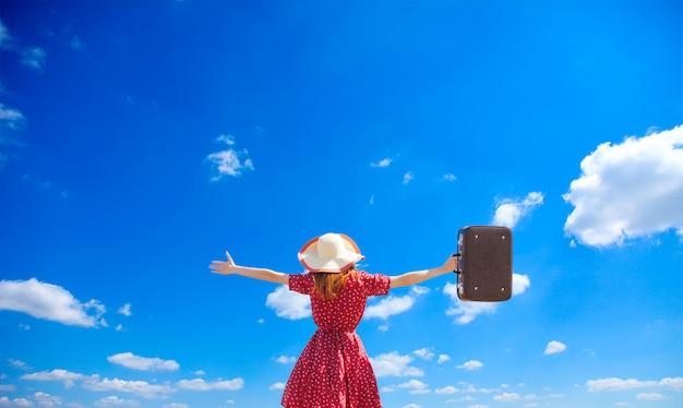 Junges mädchen mit koffer auf hintergrund des blauen himmels