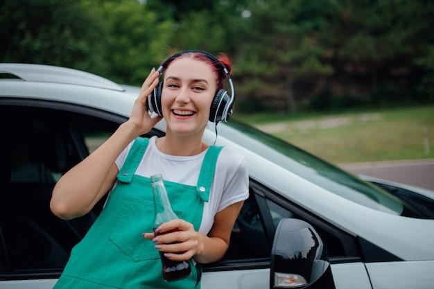 Junges mädchen mit kopfhörern, die musik neben dem auto hören