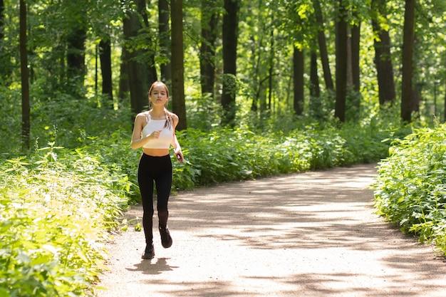 Junges mädchen mit kopfhörern geht im park joggen