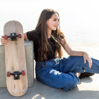 Junges mädchen mit langen haaren, die ihr skateboard draußen halten