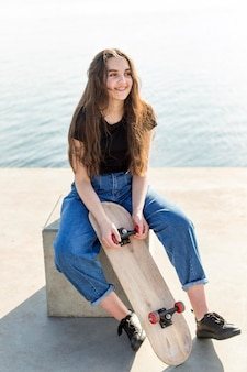 Junges mädchen mit langen haaren, die ihr skateboard halten