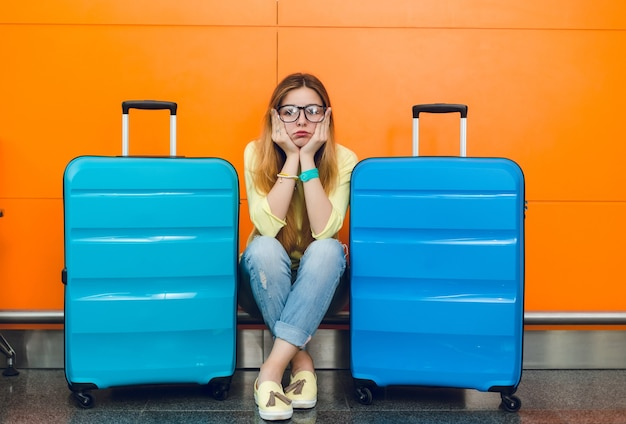 Junges mädchen mit langen haaren in gläsern sitzt auf orangefarbenem hintergrund zwischen zwei koffern. sie trägt einen gelben pullover mit jeans. sie sieht verärgert aus.