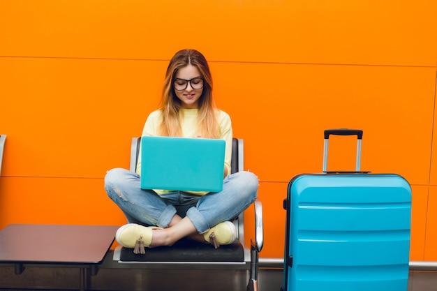 Junges mädchen mit langen haaren sitzt auf stuhl auf orange hintergrund. sie trägt einen gelben pullover und jeans. sie tippt auf einem laptop.