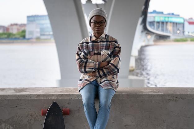Junges mädchen mit longboard sitzen auf betonpflaster schwarze frau in freizeitkleidung mit skateboard