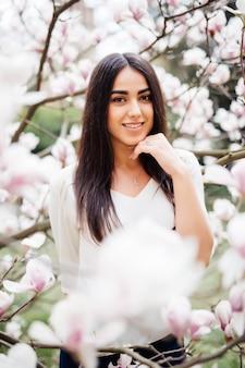 Junges mädchen mit magnolienblüte. schöne junge frau nahe frühlingsblumenbaum.