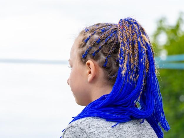 Junges mädchen mit modischer frisur mit geflochtenen blauen bändern im haar, blaues haar. ungewöhnliche frisur