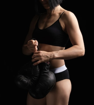 Junges mädchen mit muskulösem körper hält ein paar alte schwarze boxhandschuhe