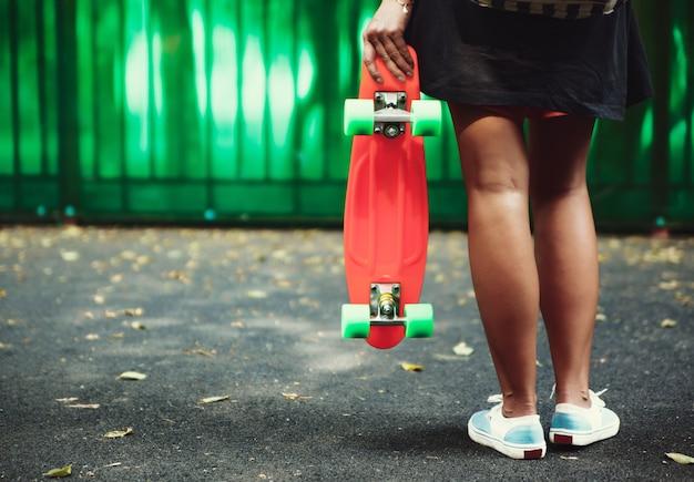 Junges mädchen mit plastik orange penny shortboard hinter grüner wand in kappe