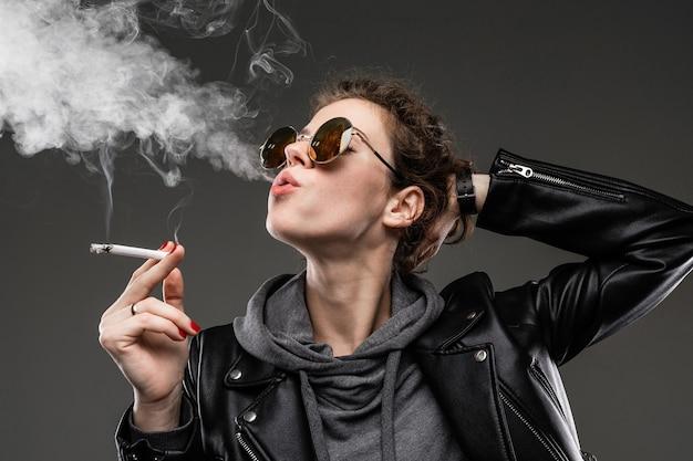 Junges mädchen mit rauen gesichtszügen in schwarzer jacke raucht isoliert