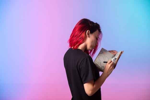 Junges mädchen mit rosa haaren, die ein skizzenbuch halten und betrachten. Kostenlose Fotos