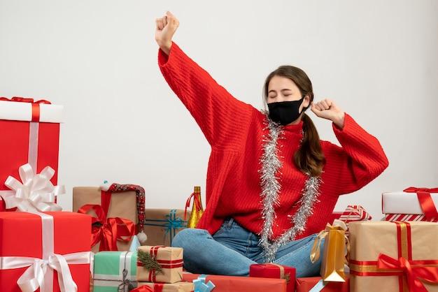 Junges mädchen mit rotem pullover und schwarzer maske, die hände öffnen, die geschenke auf weiß sitzen