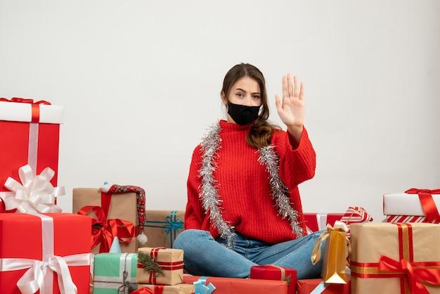 Junges mädchen mit rotem pullover und schwarzer maske, die ihre hand hebt, die um geschenke auf weiß sitzt