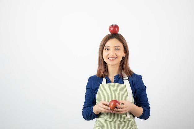 Junges mädchen mit roten äpfeln beim lächeln auf weiß.