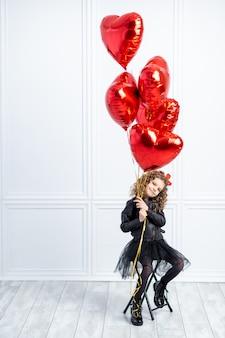 Junges mädchen mit roten luftballons
