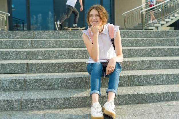 Junges mädchen mit rucksack, sitzt auf den stufen hält schulheft