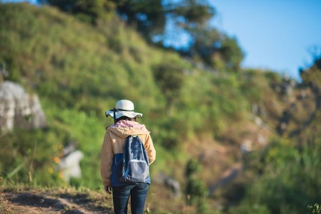 Junges mädchen mit rucksack sonnenaufgang auf höchstberg genießend