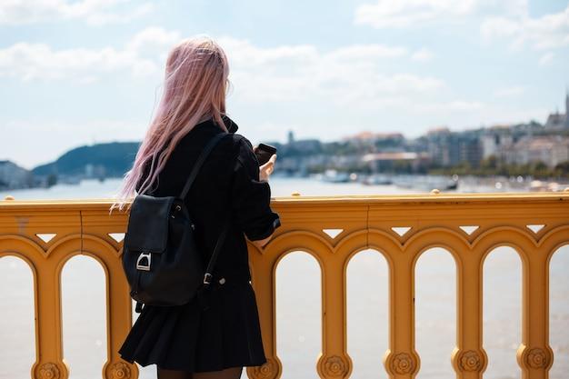 Junges mädchen mit rucksack und rosa haaren, machen sie ein foto mit smartphone von der brücke.
