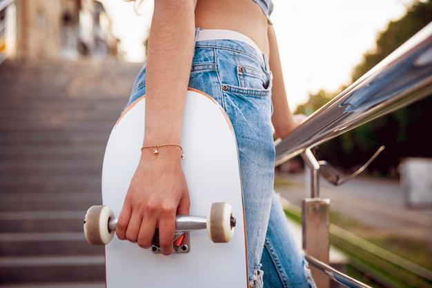 Junges mädchen mit skateboard auf der großen grauen wand.