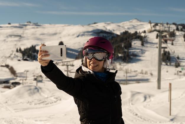Junges mädchen mit skikleidung, einer skibrille und einem skihelm, der ein selfie in einem skigebiet macht