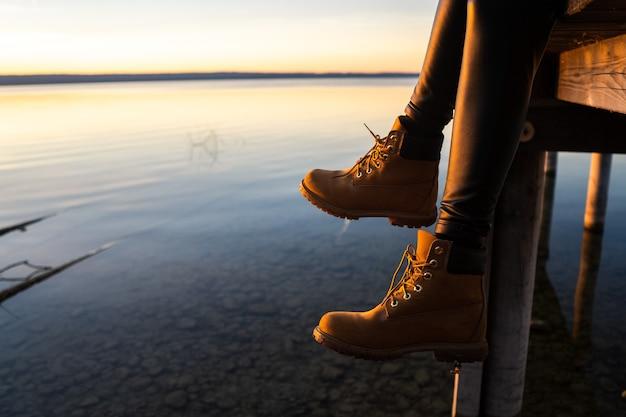 Junges mädchen mit stiefeln, das während des sonnenuntergangs auf einem pier sitzt