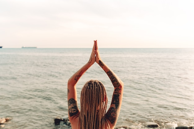 Junges mädchen mit tätowierung praktiziert yoga auf see. gesten der meditation. blick von hinten
