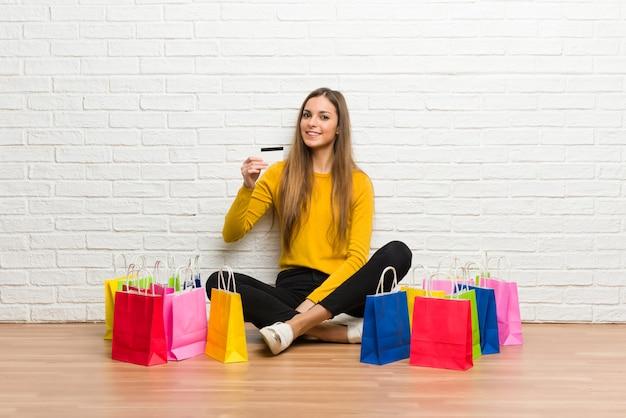 Junges mädchen mit vielen einkaufstaschen, die eine kreditkarte halten