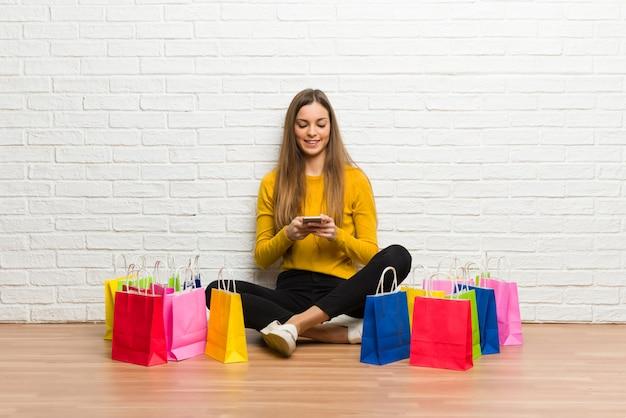 Junges mädchen mit vielen einkaufstaschen, die eine mitteilung mit dem mobile senden