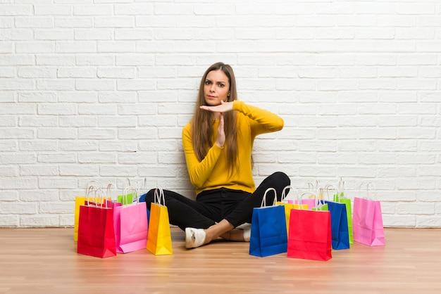 Junges mädchen mit vielen einkaufstaschen, die halt machen, mit ihrer hand zu gestikulieren, um eine tat zu stoppen