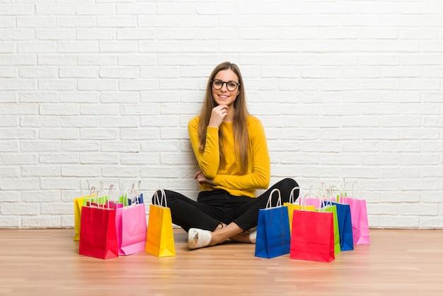 Junges mädchen mit vielen einkaufstüten mit brille und lächelnd