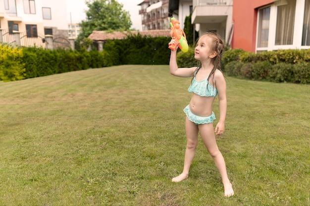 Junges mädchen mit wasserpistole