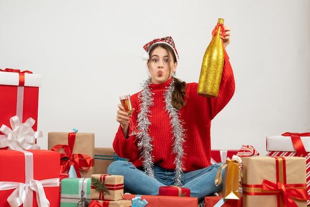 Junges mädchen mit weihnachtsmütze, die champagner und glas hält, die herum geschenke auf weiß sitzen