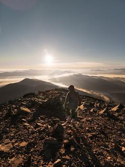 Junges mädchen oben auf dem berg am morgen bei sonnenaufgang. wandern in den bergen.